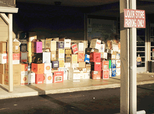 Stacks of empty beer, wine, and the liquor boxes in front of a liquor store